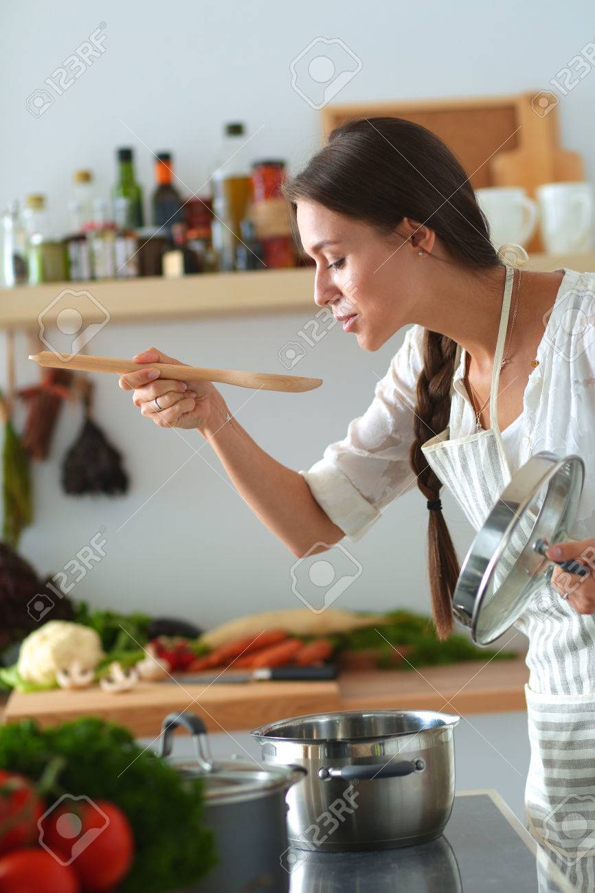 Cooking woman in kitchen with wooden spoon. - 53915980