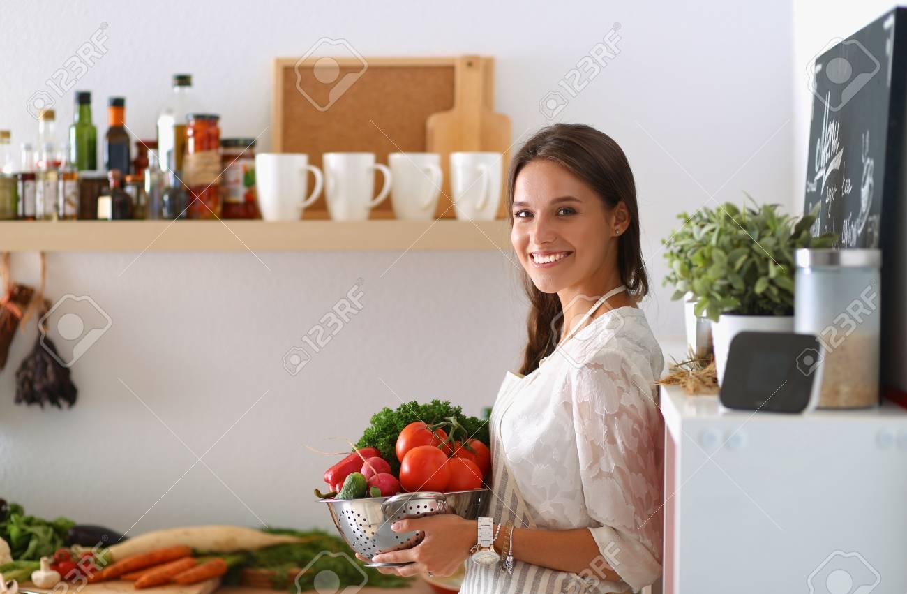 Sonriendo Mujer Con Verduras Jóvenes De Pie En La Cocina Fotos ...