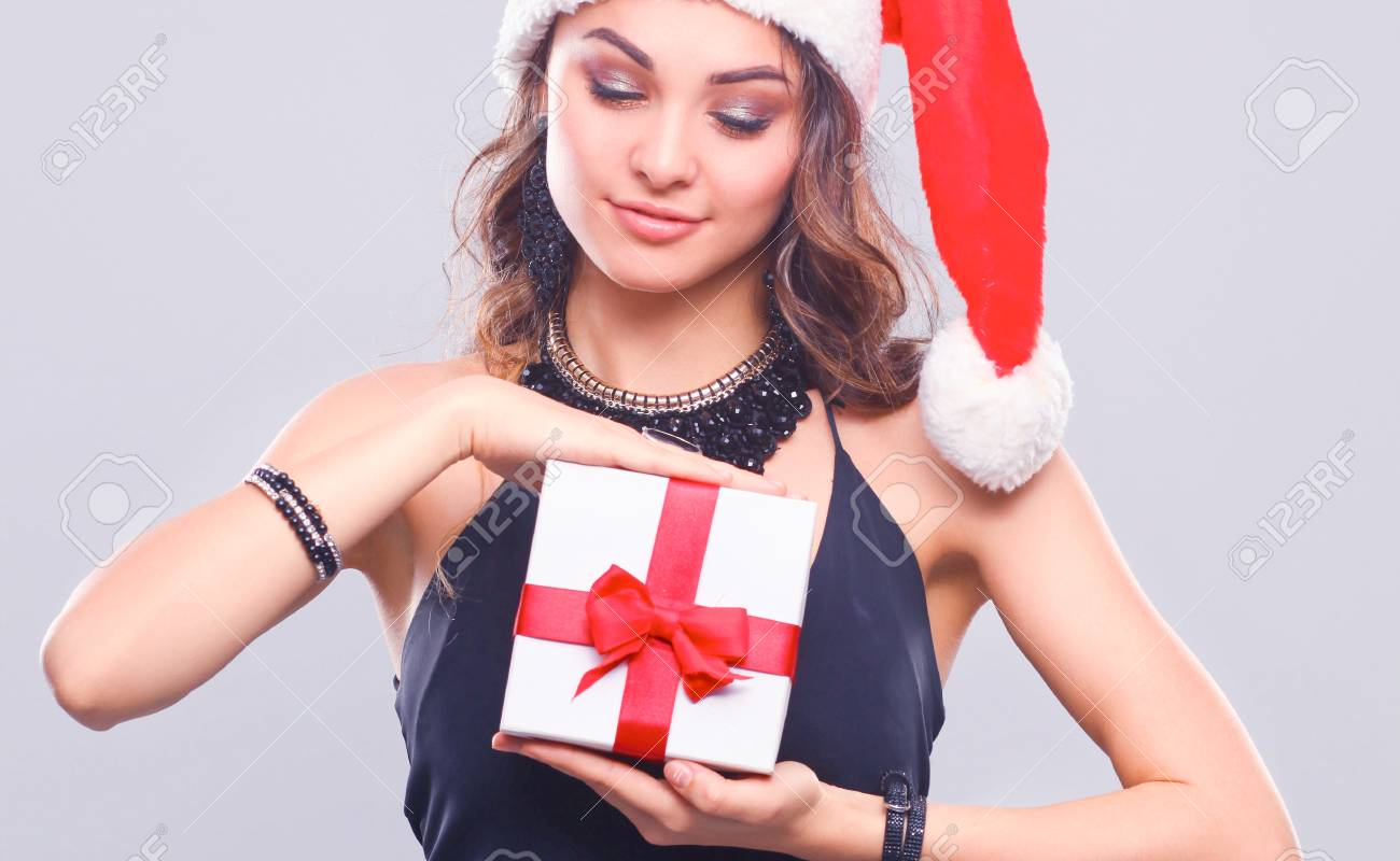 9414847b5ad5d Young Happy Woman In Santa Hat Holding Christmas Gift Stock Photo ...