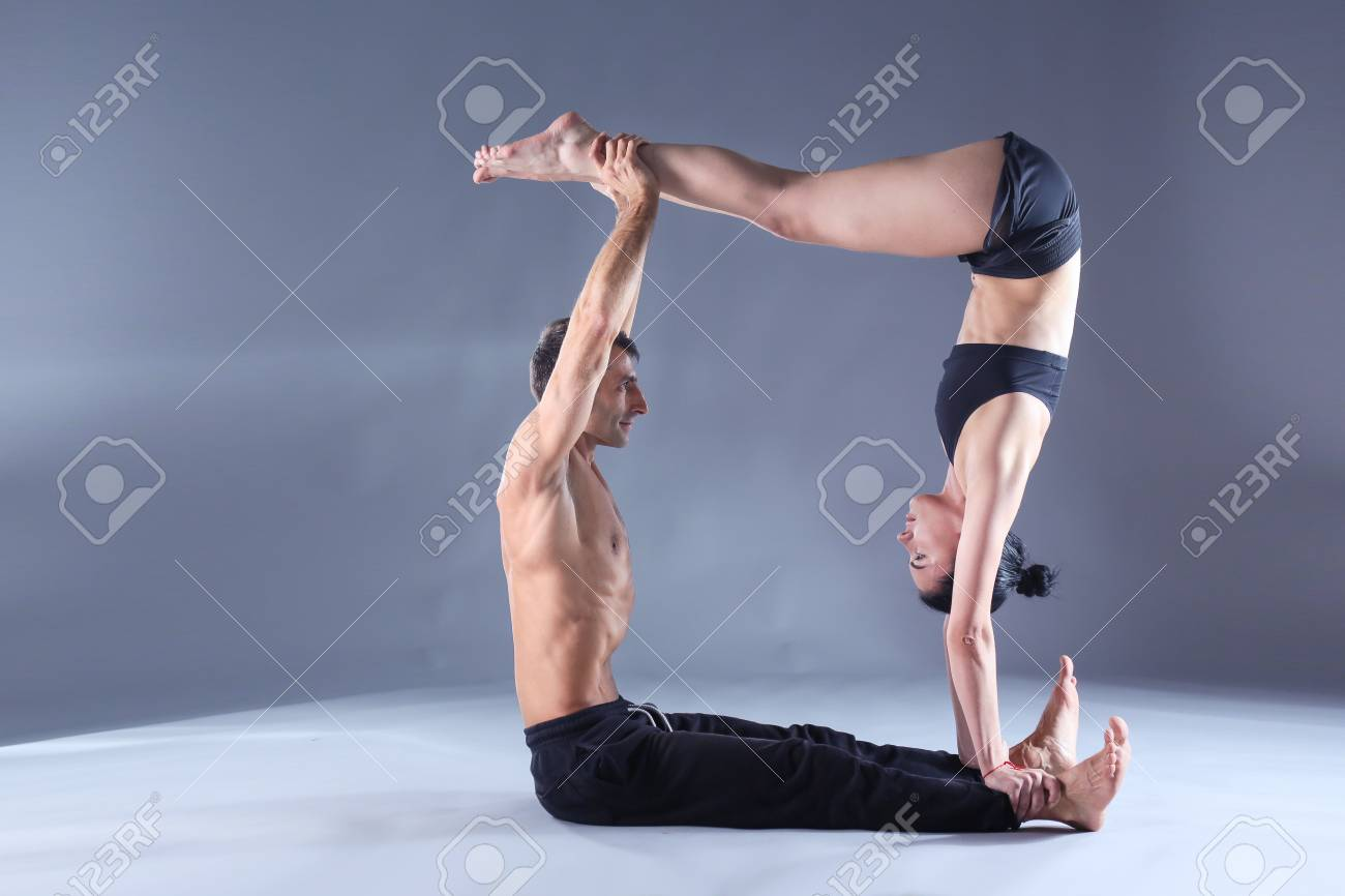 Young Couple Practicing Acro Yoga On Mat In Studio Together Stock Photo Picture And Royalty Free Image Image 91023504