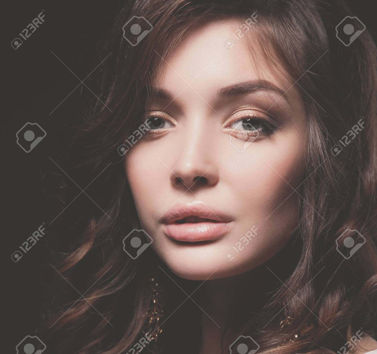 Portrait of beautiful young woman face. Isolated on dark background. - 121277110