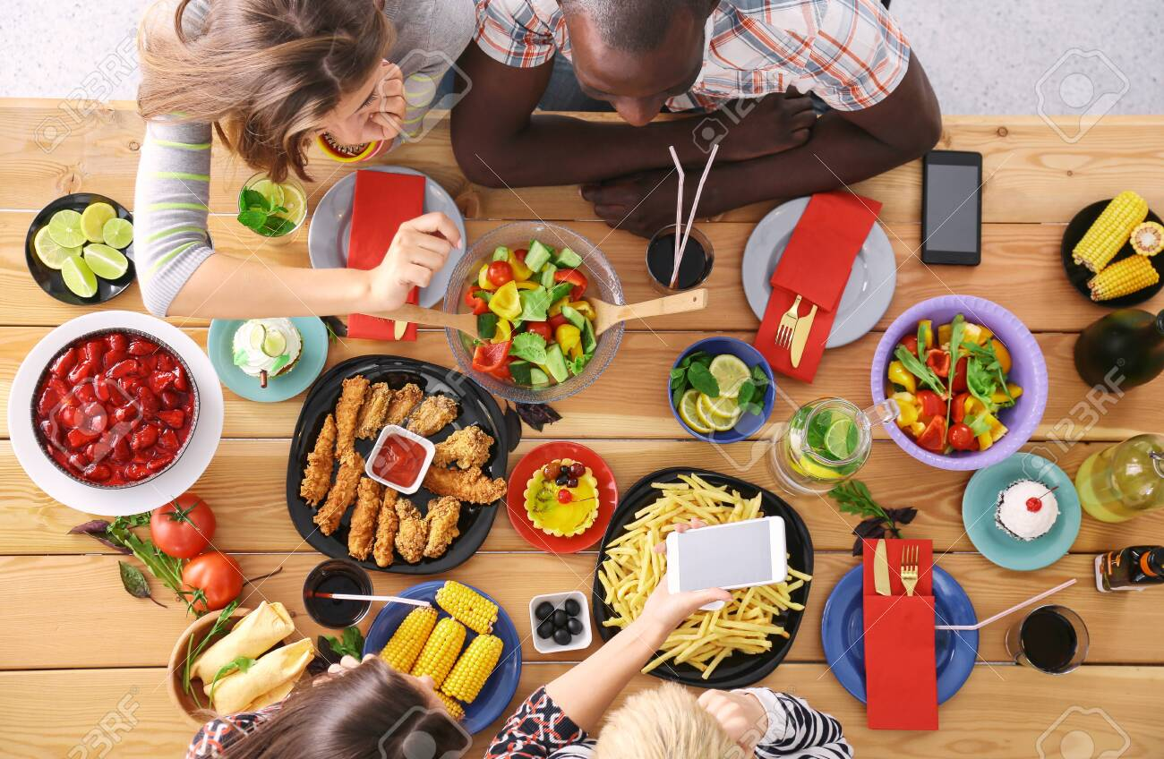 Top view of group of people having dinner together while sitting at wooden table. Food on the table. People eat fast food. - 129463705