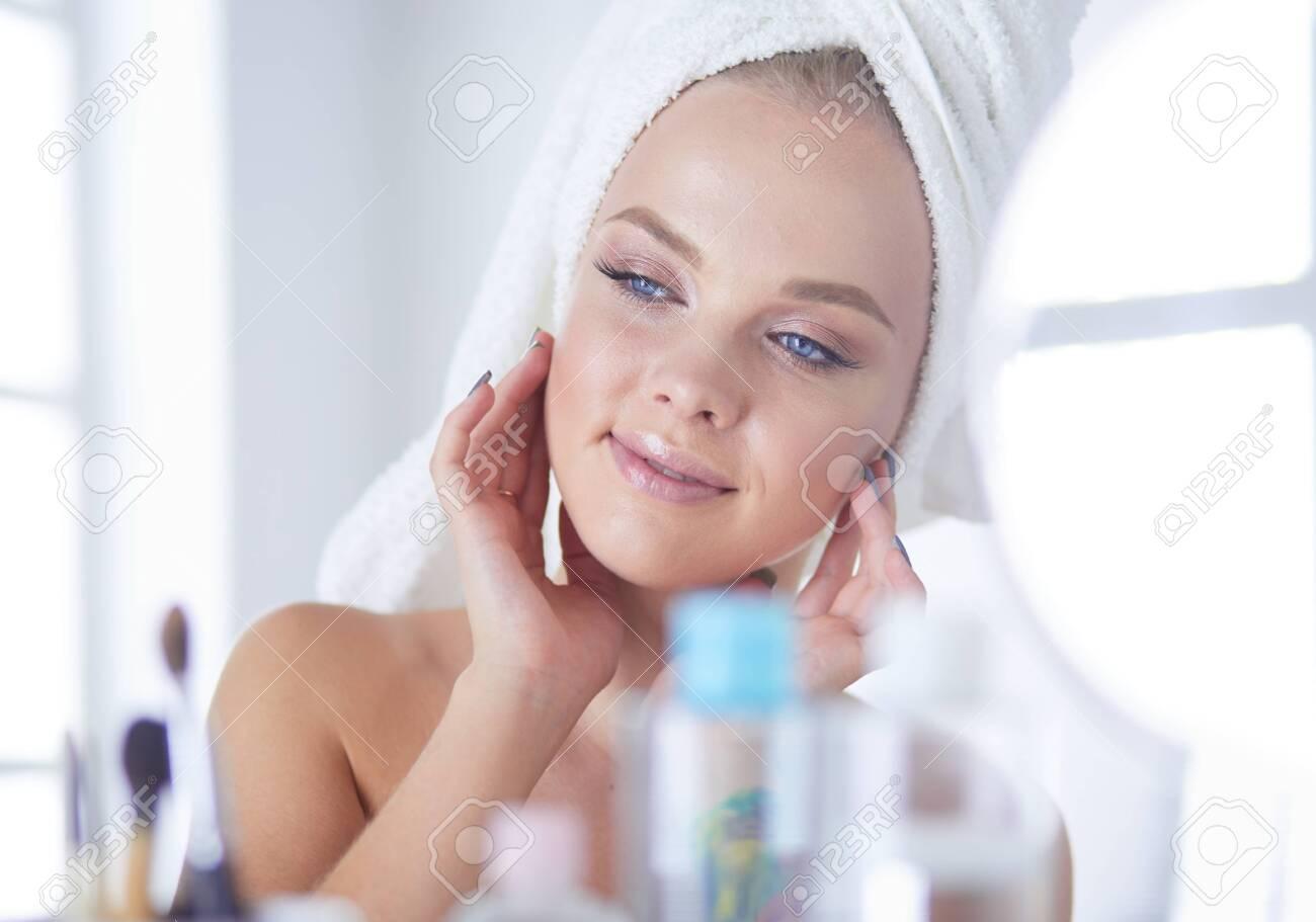 Young woman in bathrobe looking in bathroom mirror - 130392559