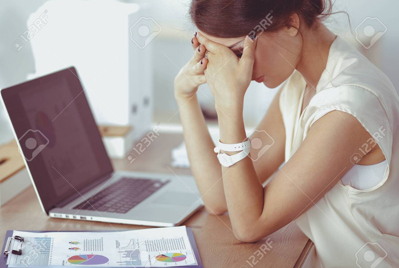 Portrait of tired young business woman with laptop computer - 141145591