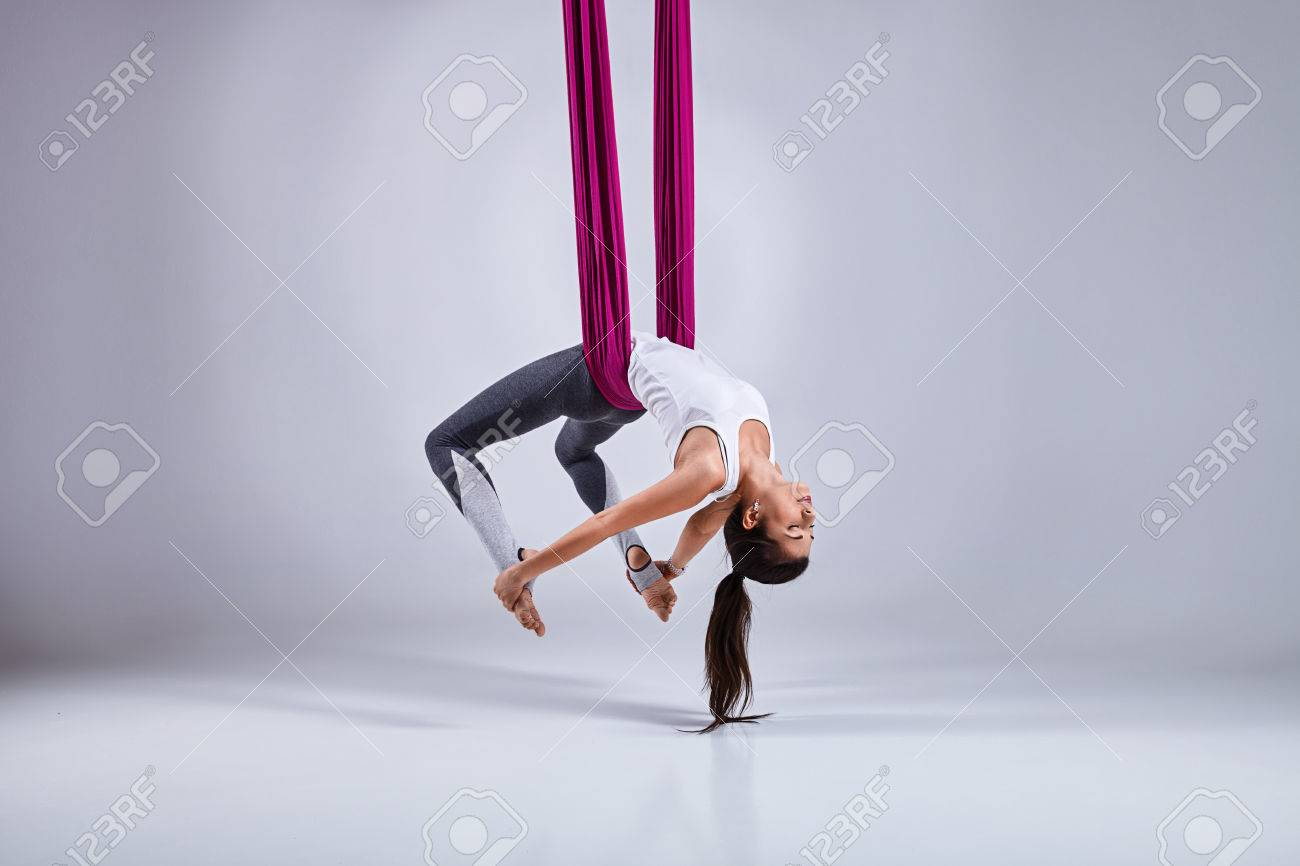 Young woman practices aerial different inversion anti-gravity yoga with a hammock in a white studio. Concept of a mental and physical health an harmony living - 66147517