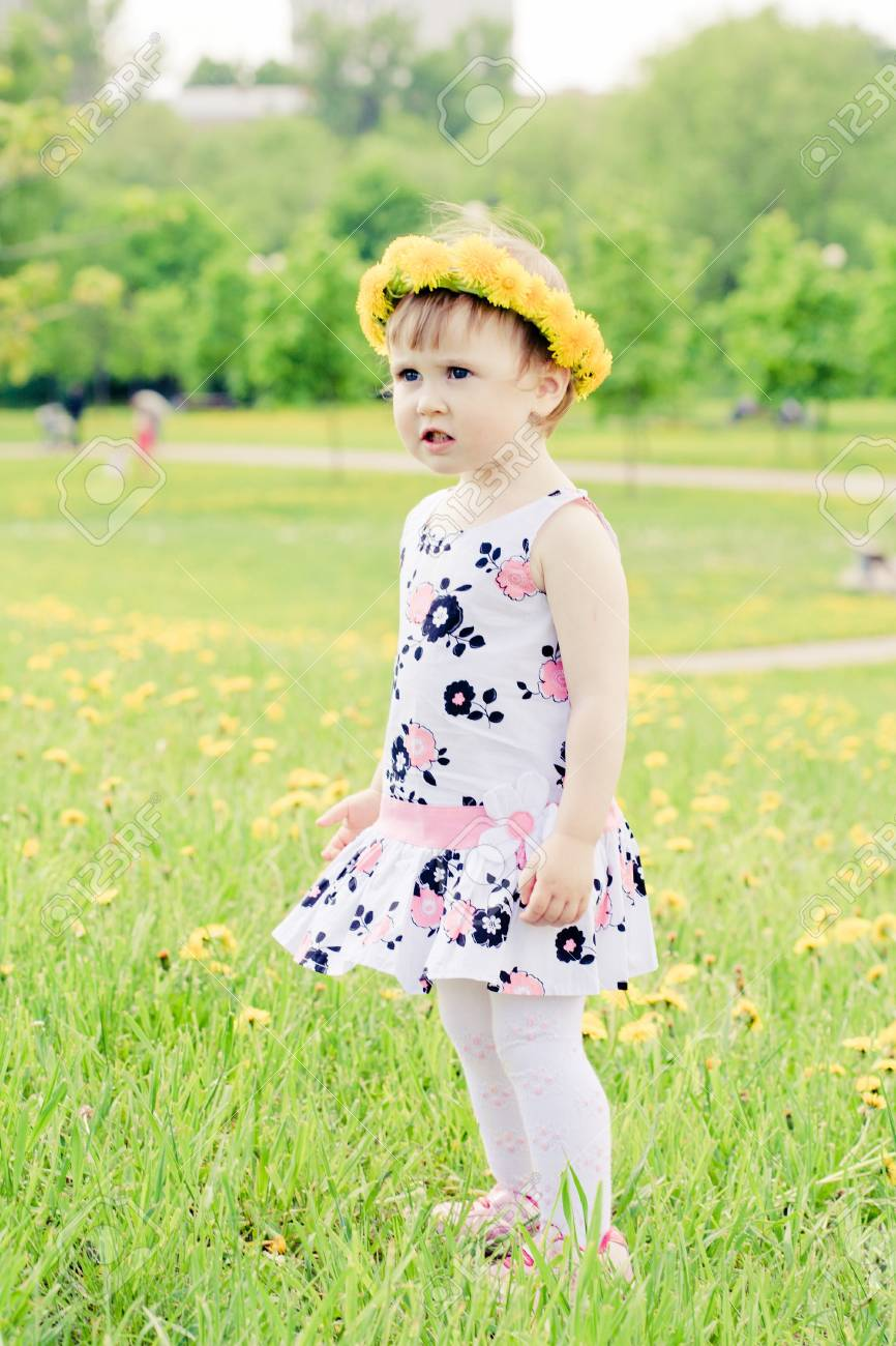 little girl walks on a glade with dandelions Stock Photo - 9917903