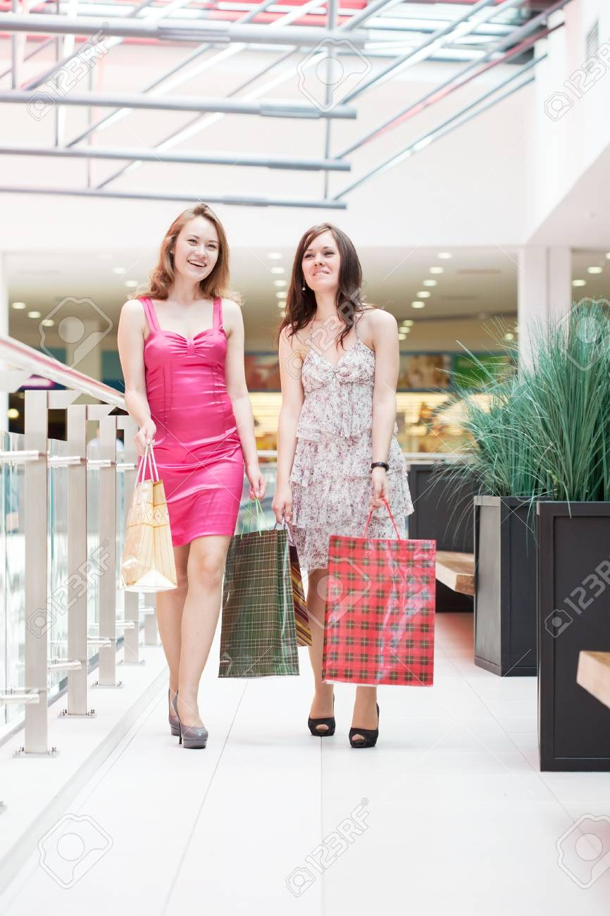 Two friends with purchases in the big shopping center Stock Photo - 9918827