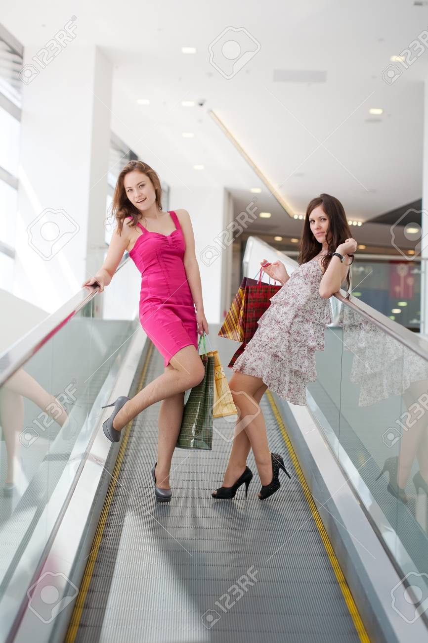 Two friends with purchases on the escalator in the big shopping center Stock Photo - 9918073