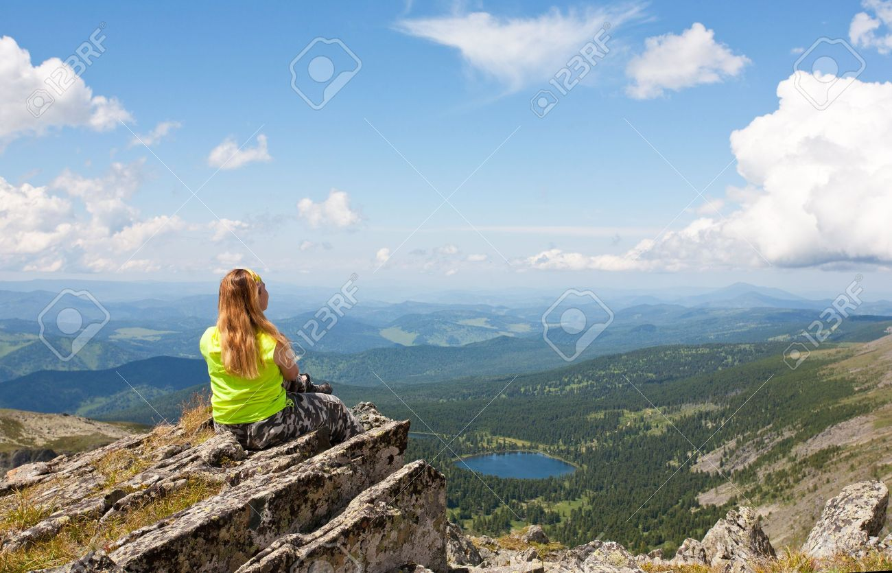 girl sits on a rock and looks at mountain lake Stock Photo - 10604100