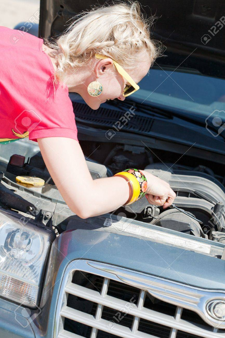 Blonde woman trying to fix the car Stock Photo - 10788405