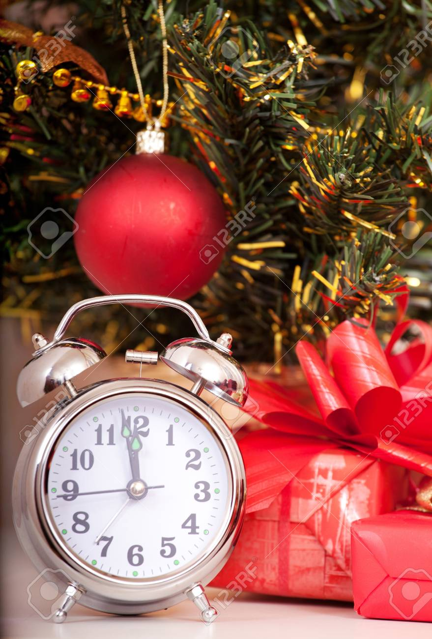 Soon new year! Hours and a gift stand under a fir-tree Stock Photo - 11074026