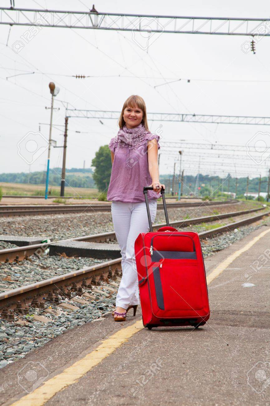 woman with luggage waiting train on railroad Stock Photo - 13296592