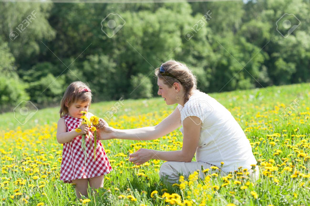 Mother with the small daughter play on a glade with dandelions Stock Photo - 19652976