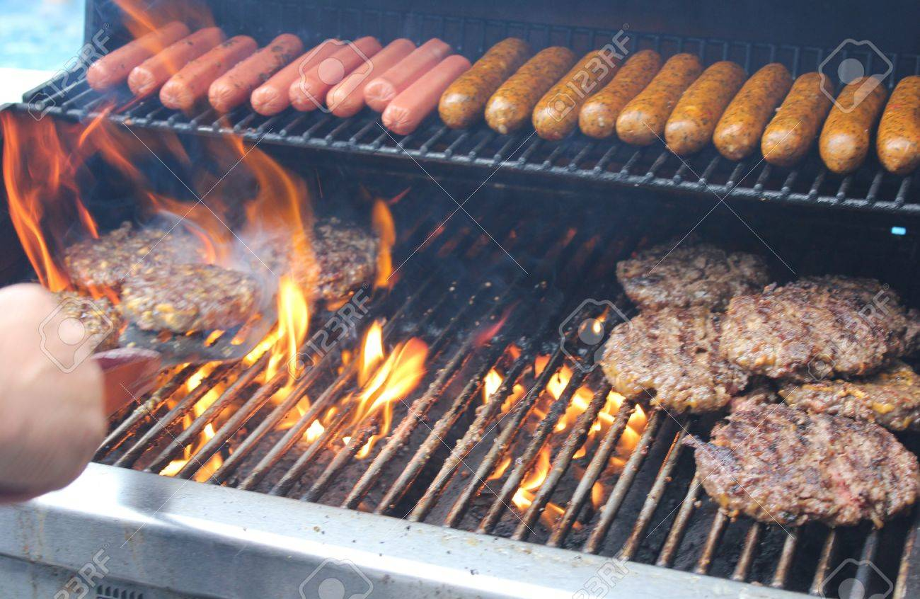 flames flare up as dogs and hamburgers being tended by the