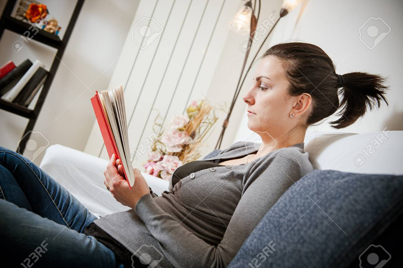Woman lying on a sofa and holding a book in a living room,Italy Stock Photo - 17669747