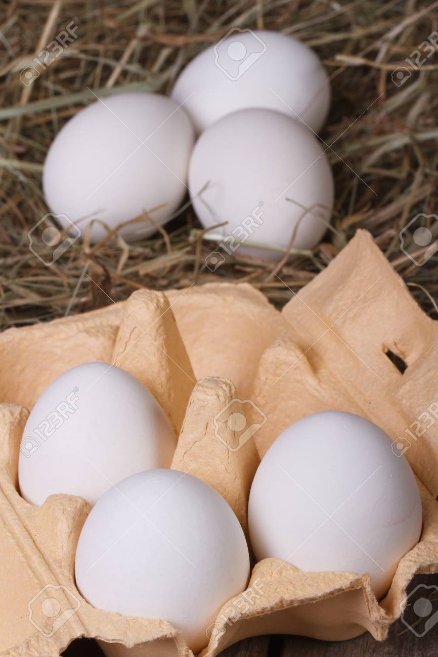 white chicken eggs in a tray and a hay closeup. vertical Stock Photo - 25784496
