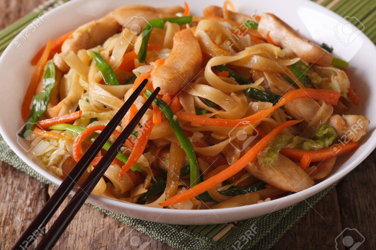 Chinese Food: Chow Mein With Chicken And Vegetables On A Table Close Up.