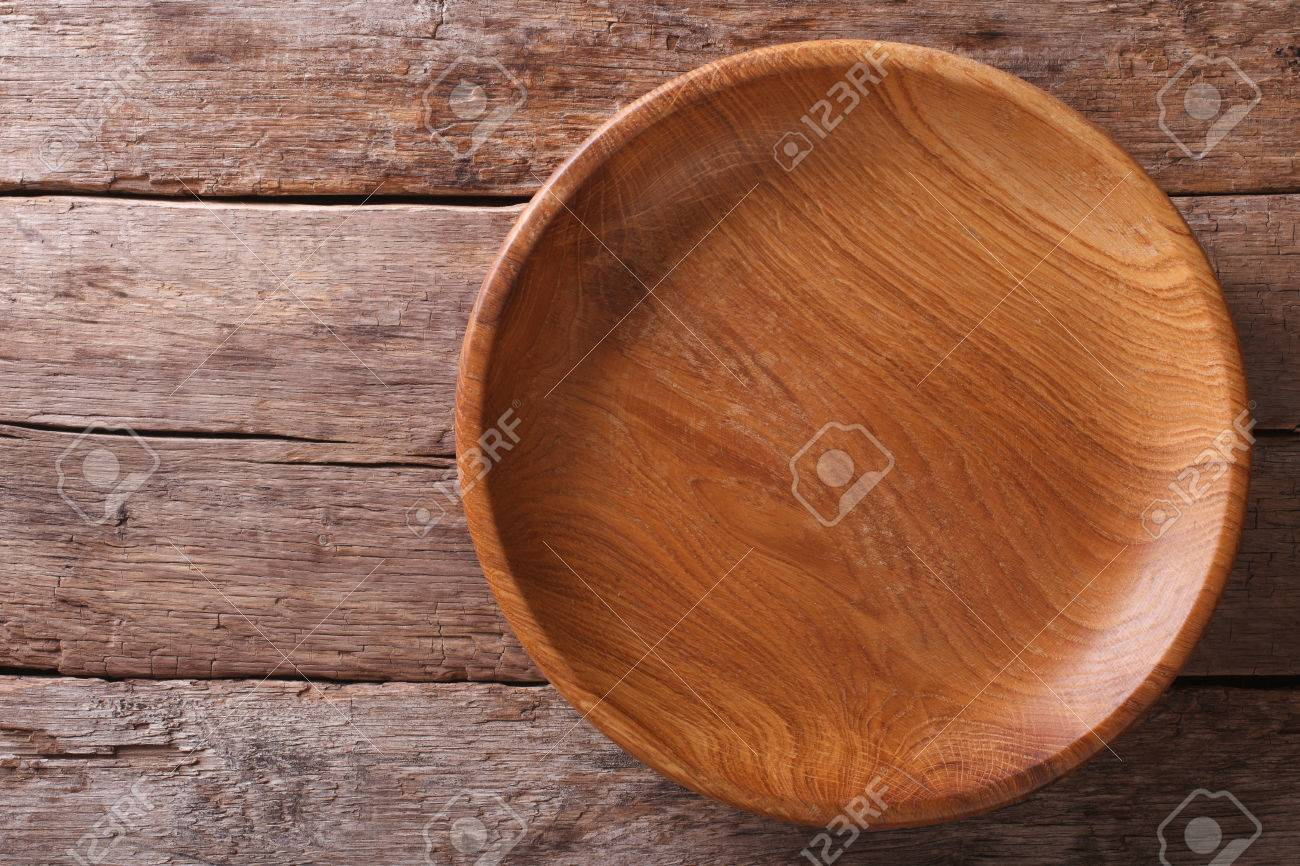 Stock Photo   The Brown Wooden Plate On A Rustic Table Closeup