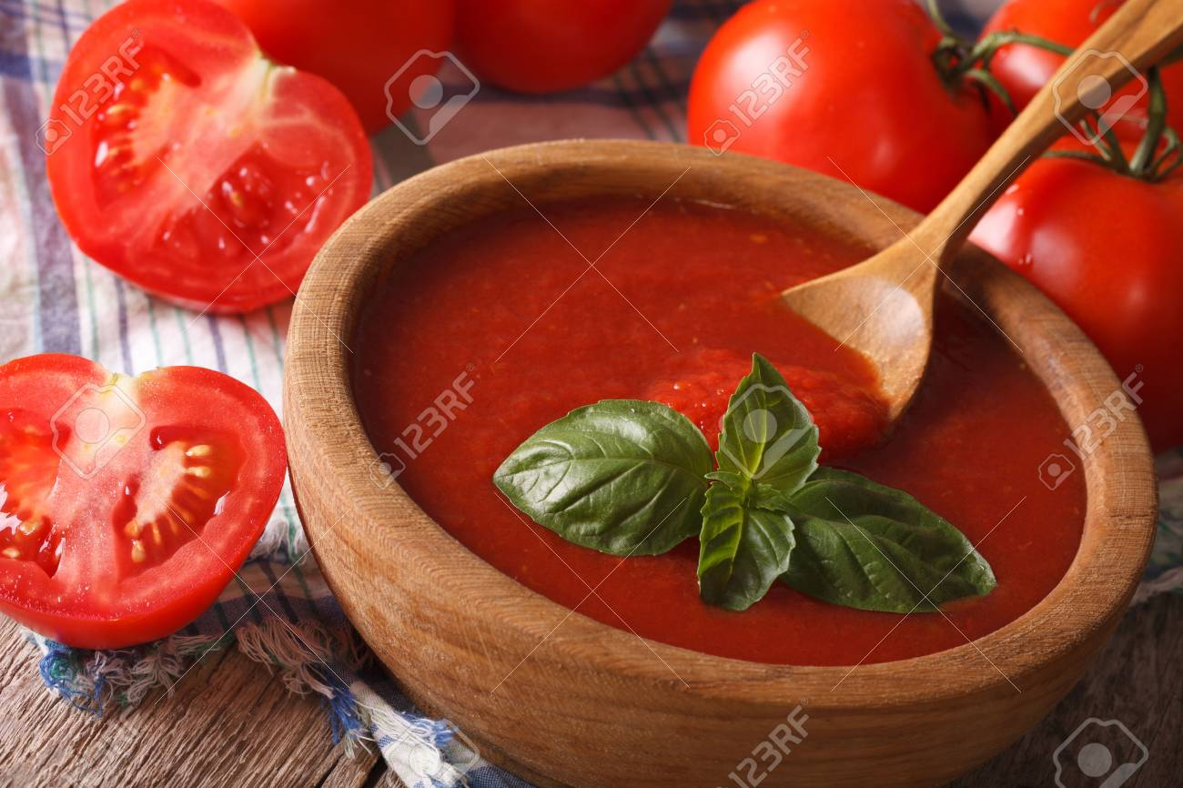 Fresh red tomato sauce with basil in a wooden bowl closeup. Horizontal - 45030638