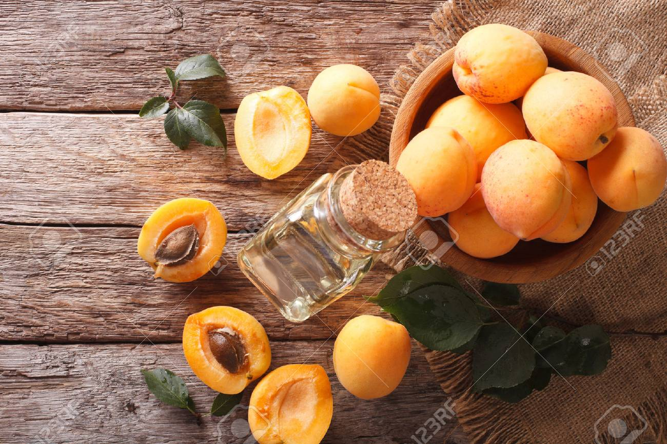 apricot kernel oil in a glass jar closeup on the table. Horizontal view from above - 60306176