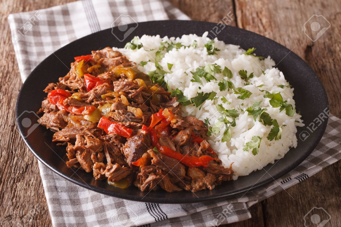 Mexican food ropa vieja: beef stew in tomato sauce with vegetables and rice garnish on a plate close-up. Horizontal - 62706851