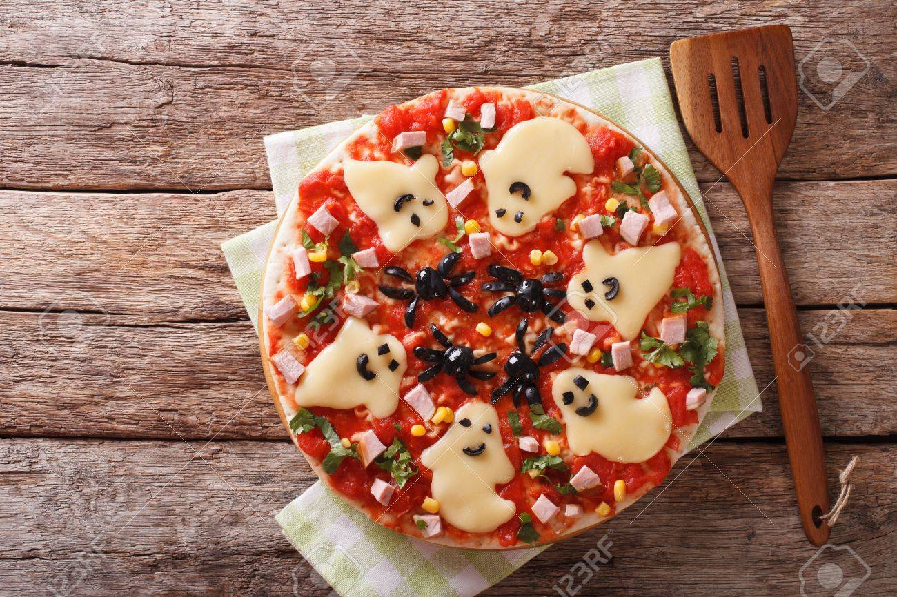 Halloween Food: Pizza with ghosts and spiders close-up on the table. horizontal view from above - 62706861