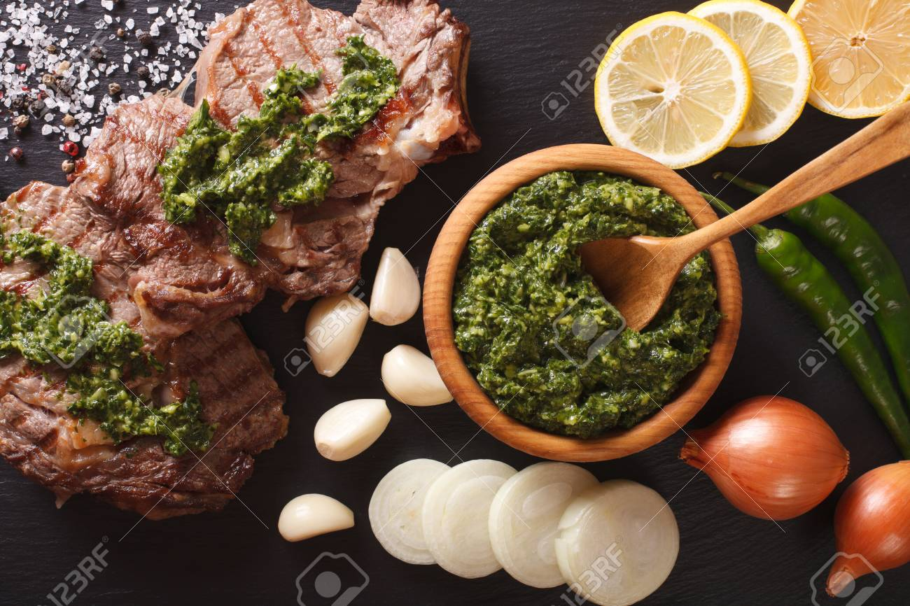 Argentine cuisine: grilled beef steak with chimichurri sauce macro on the table. horizontal view from above - 62706927