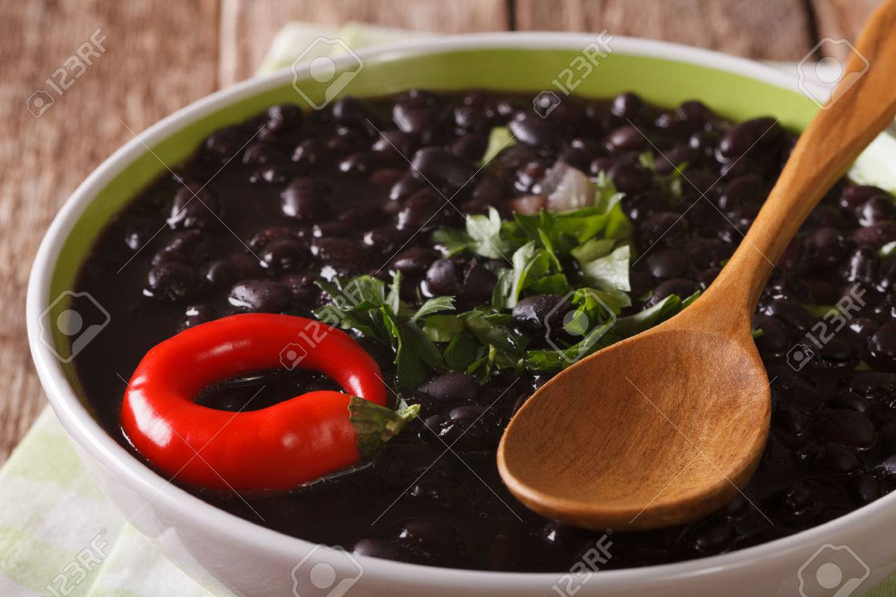 Stewed spicy black beans close up in a bowl on the table. Horizontal - 64348142