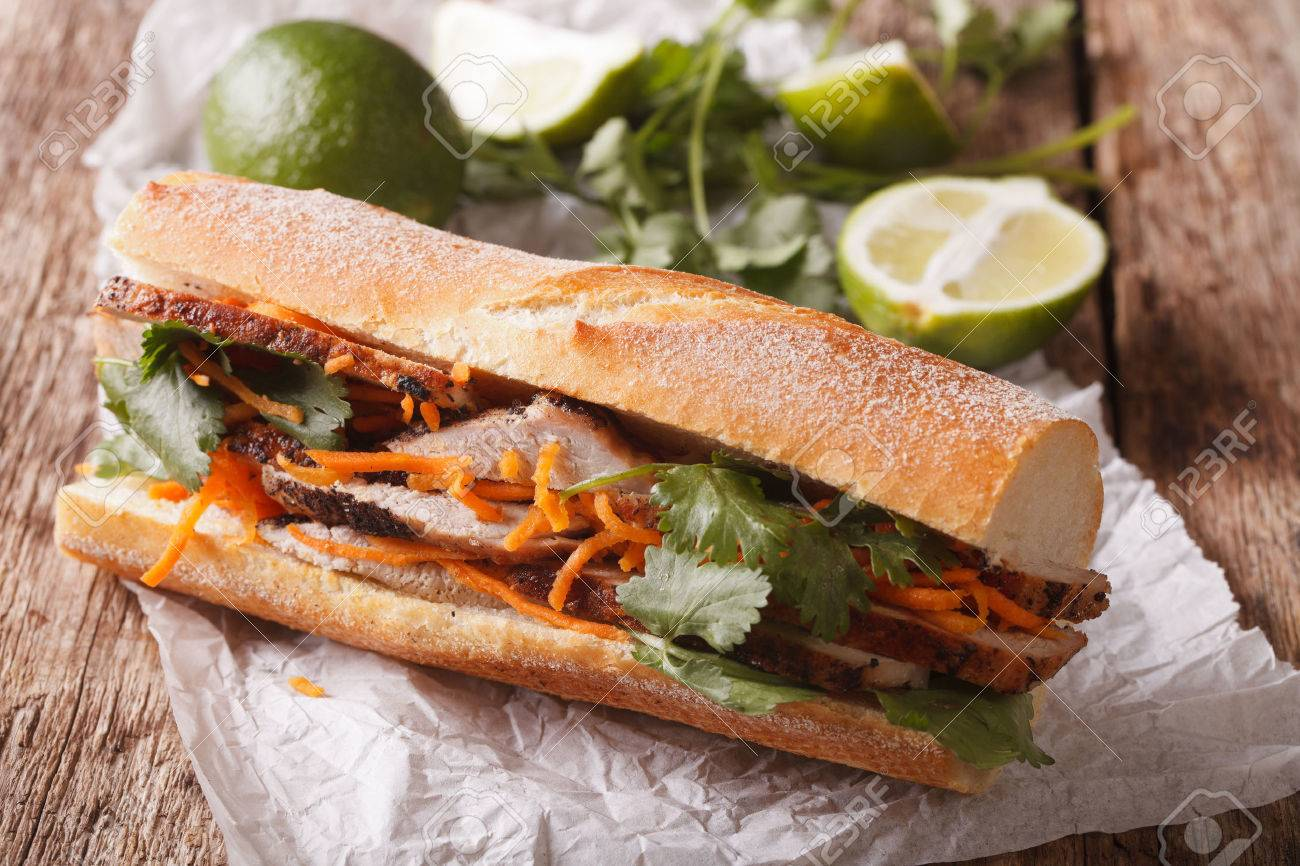 Vietnamese Pork Banh Mi Sandwich with Cilantro and carrot close-up on the table. Horizontal - 64385136