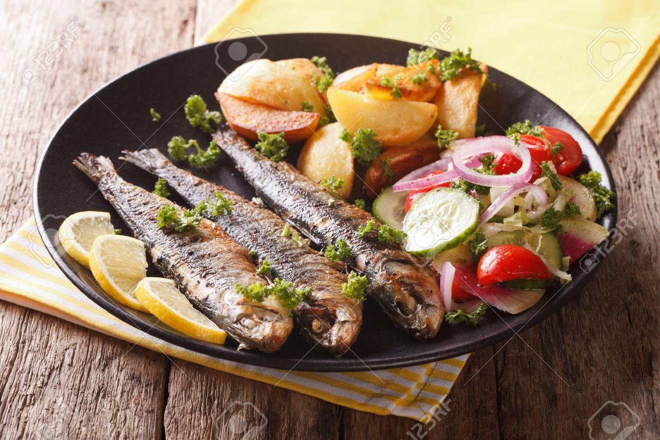 Fried sardines with roasted potatoes and fresh salad on the plate closeup. horizontal - 66572979