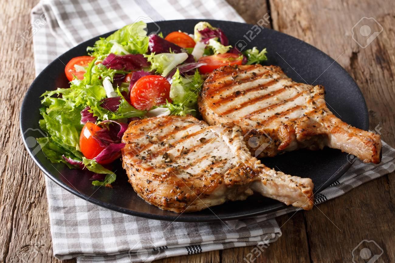 Grilled pork steak with bone, fresh vegetable salad close-up on plate. Horizontal - 75488495