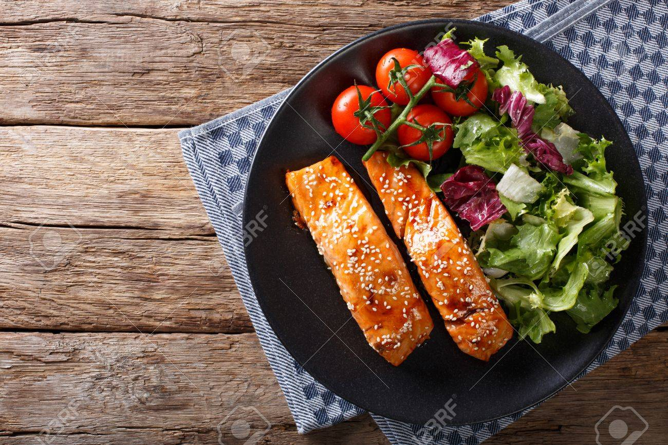 Salmon with sesame seeds in Asian style and fresh salad close-up on a plate. horizontal view from above - 76503978