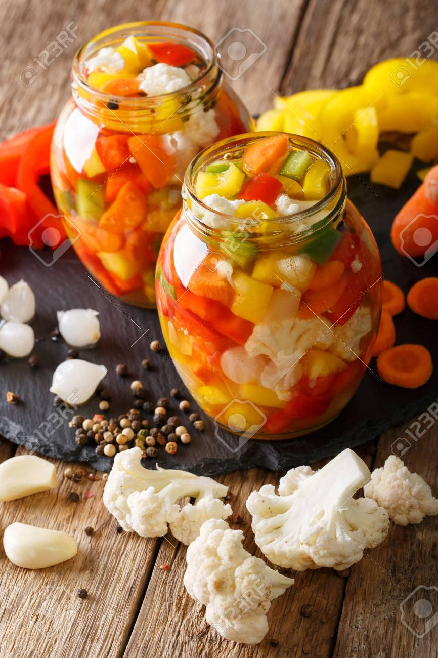 Spicy Homemade Pickled Giardiniera with Peppers, Carrots and Cauliflower close-up in glass jars. Vertical - 80037499