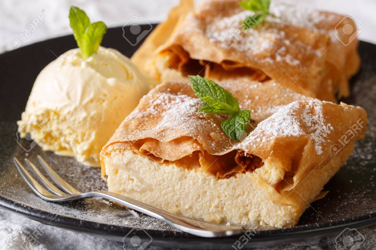 Beautiful strudel with cottage cheese, with vanilla ice cream close-up on a plate on a table. horizontal - 81432702