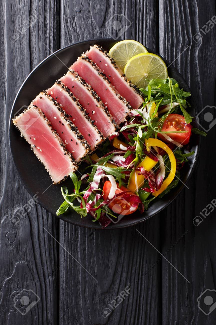 Close up of rare seared Ahi tuna slices with fresh vegetable salad on a plate. Top view from above vertical - 85253268