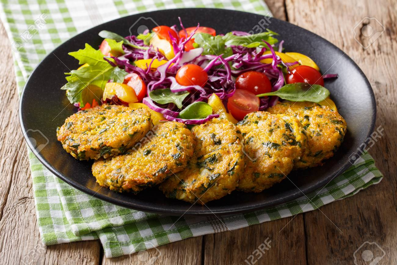Vegetarian Food: Quinoa fritters with spinach, carrots and salad of fresh vegetables close-up on a plate. horizontal - 87418839