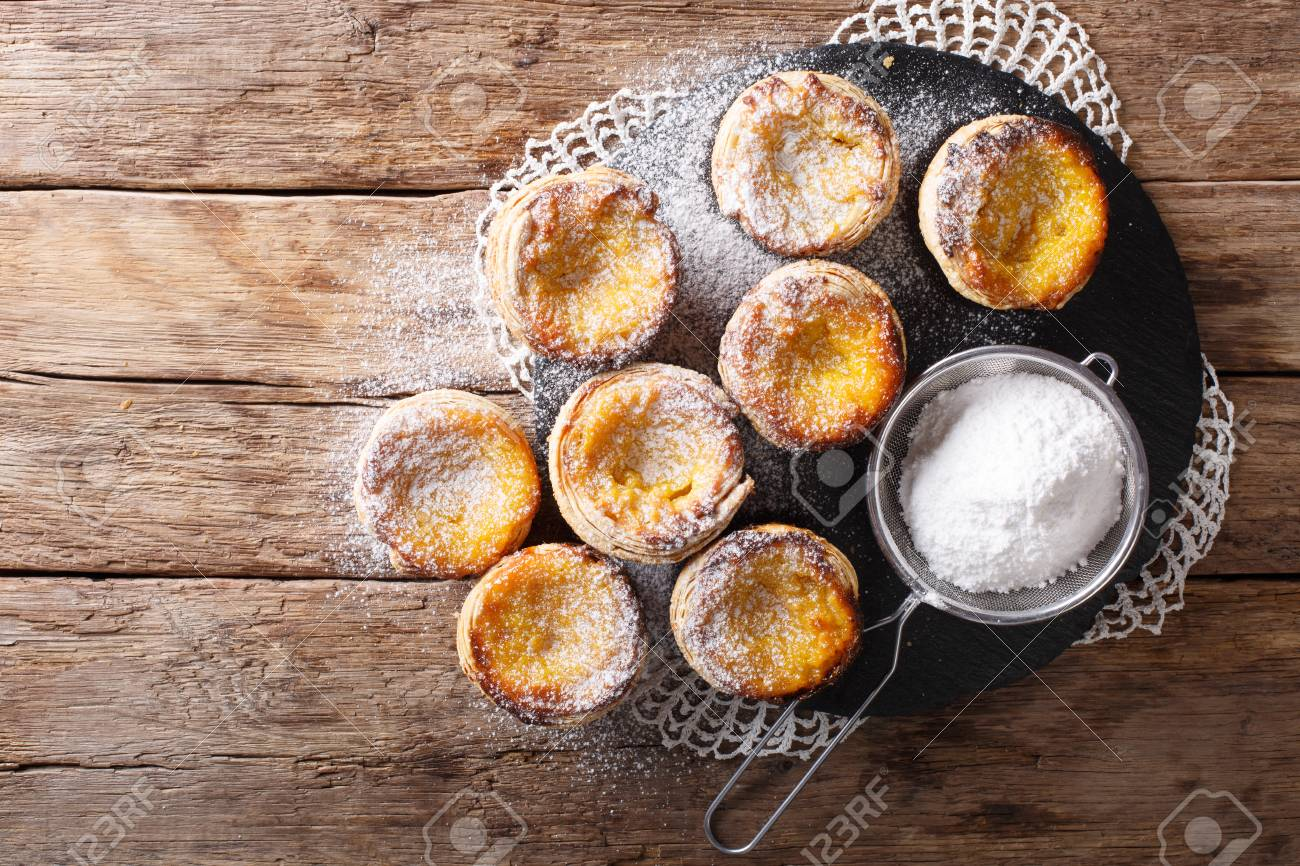 Fresh pastry dessert Pastel de nata with custard, sprinkled with powdered sugar close-up on the table. Horizontal top view from above - 94230265