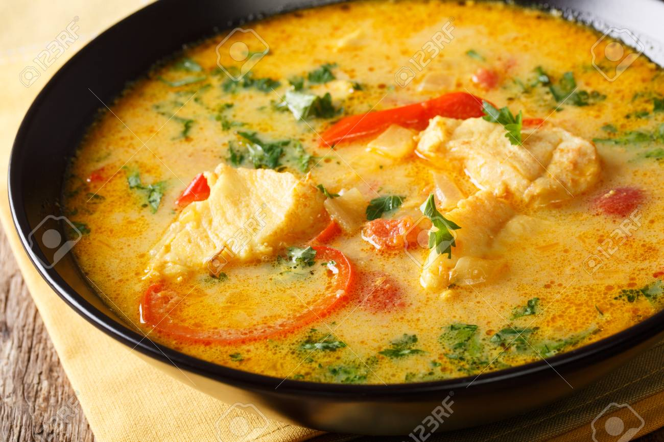 Brazilian fish Stew (Moqueca Baiana) with vegetables and coconut milk close-up on a plate on a table. Horizontal - 94388699