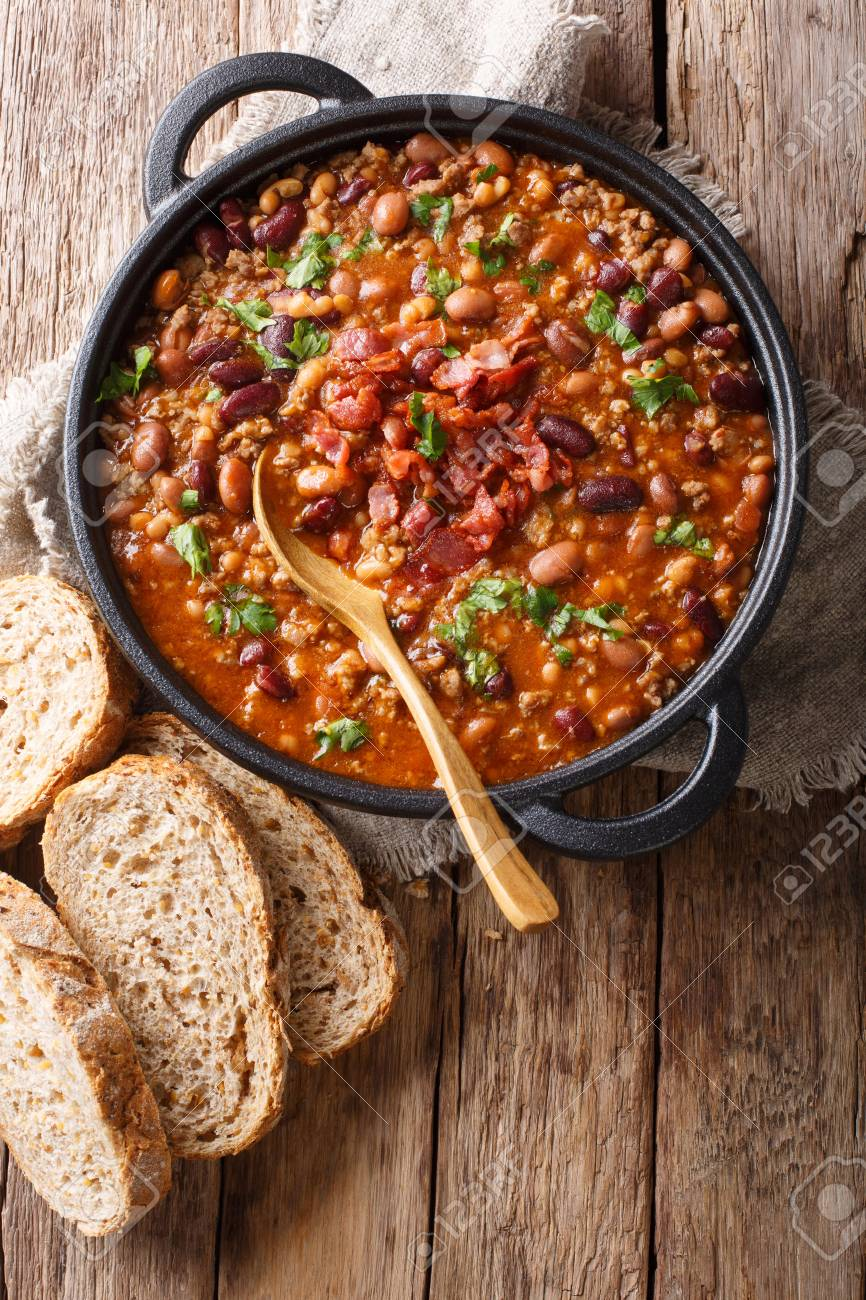 Delicious cowboy stew of beans with ground beef, bacon in a spicy sauce closeup in a bowl on the table. Vertical top view from above - 116481338