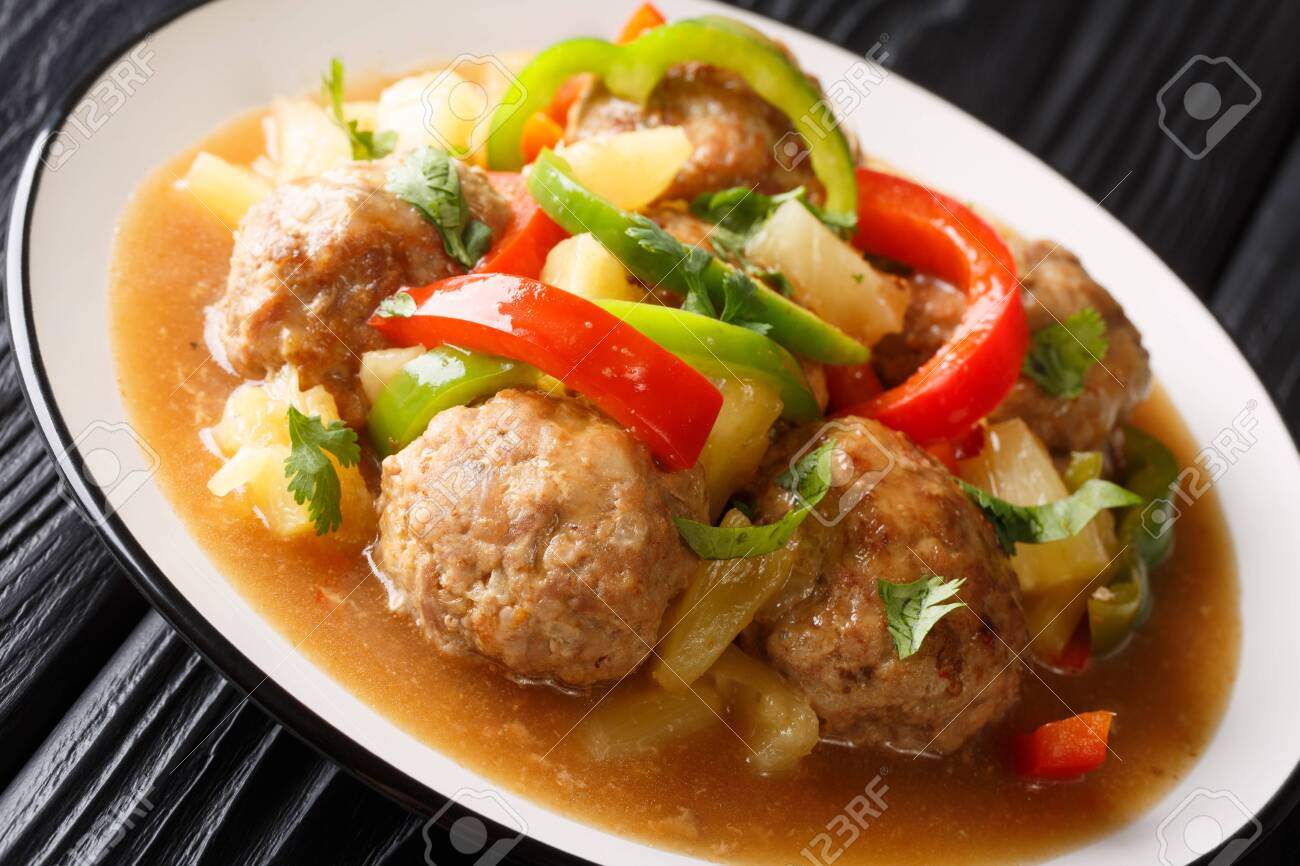 Meatballs cooked with fresh pineapples and vegetables in a sweet and sour sauce closeup on a plate on the table. horizontal - 128682030