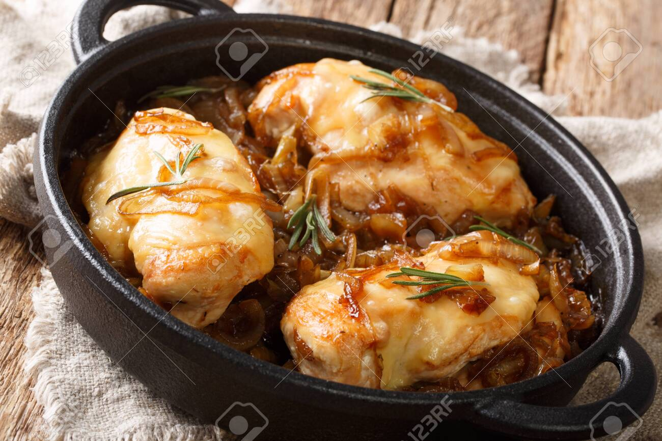 French chicken onion fillet cooked with gruyere cheese and spicy wine sauce close-up in a pan on the table. horizontal - 130585689