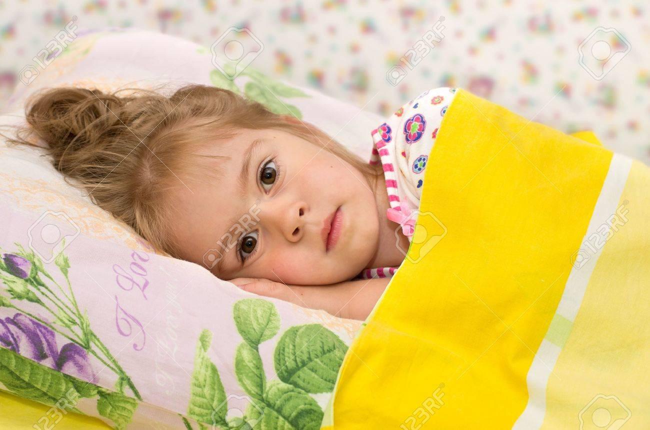 La bambina a letto. una bambina a letto con gli occhi tristi foto ...