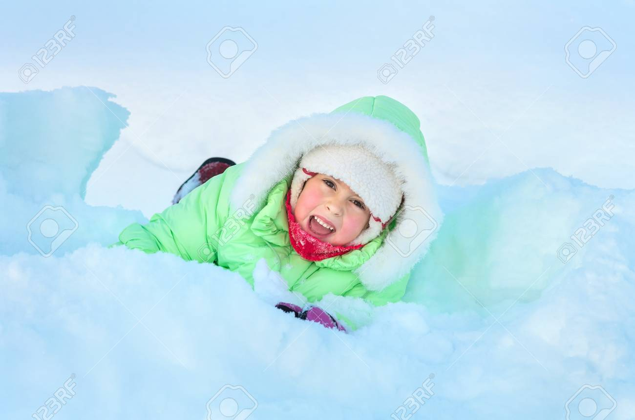 Cheerful girl lying in deep snow drift Stock Photo - 17154434