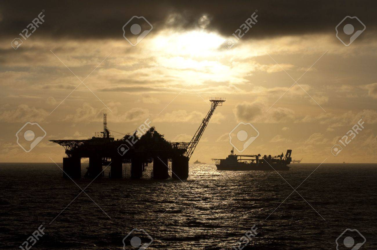 Oil rigs and supply vessels in oil rig field in Campos basin, Brazil.  Sunset time Stock Photo - 8732259
