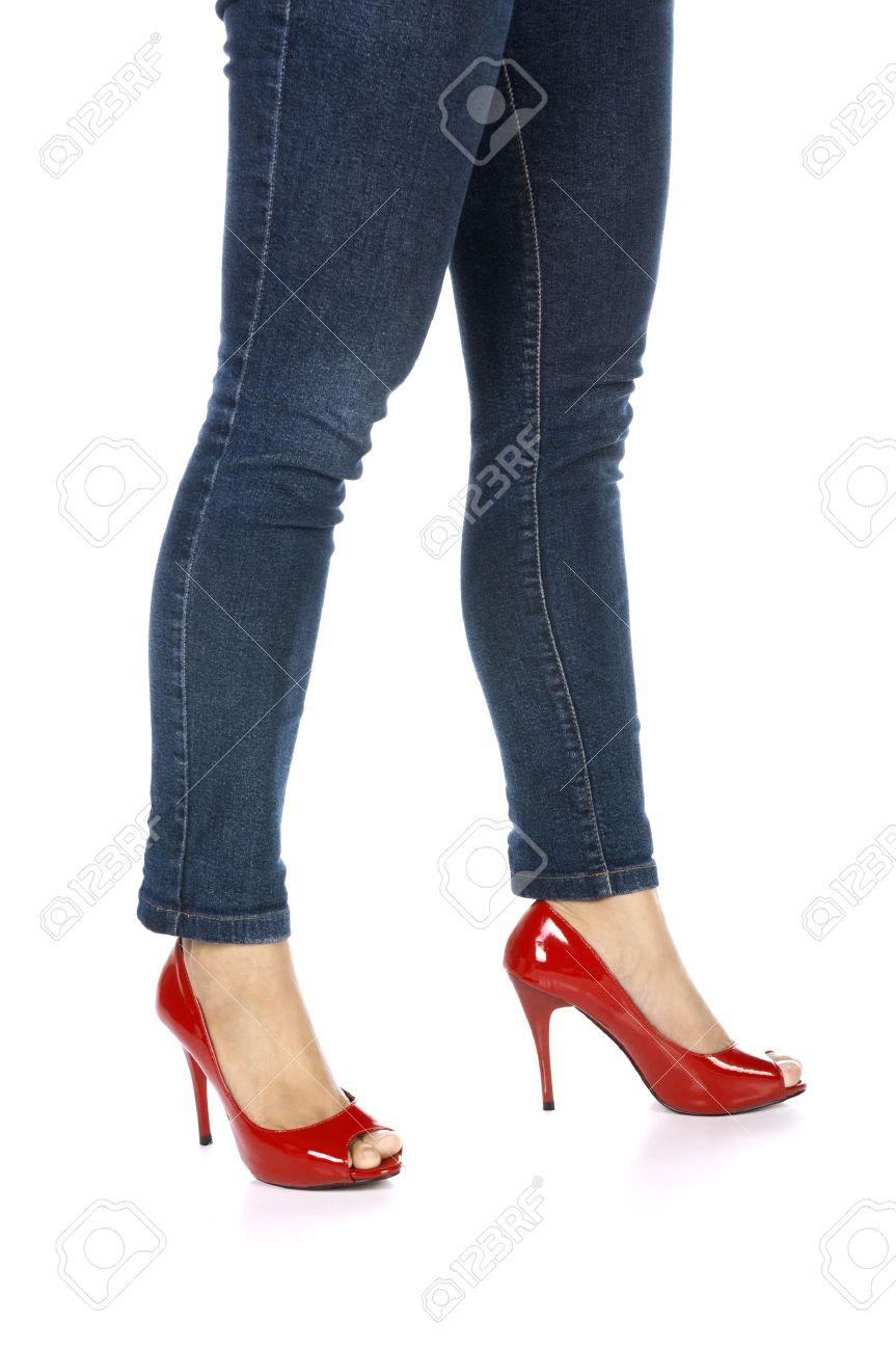 b7df419aac Bonitas piernas femeninas en zapatos rojos de tacón alto y los pantalones  vaqueros aisladas sobre fondo