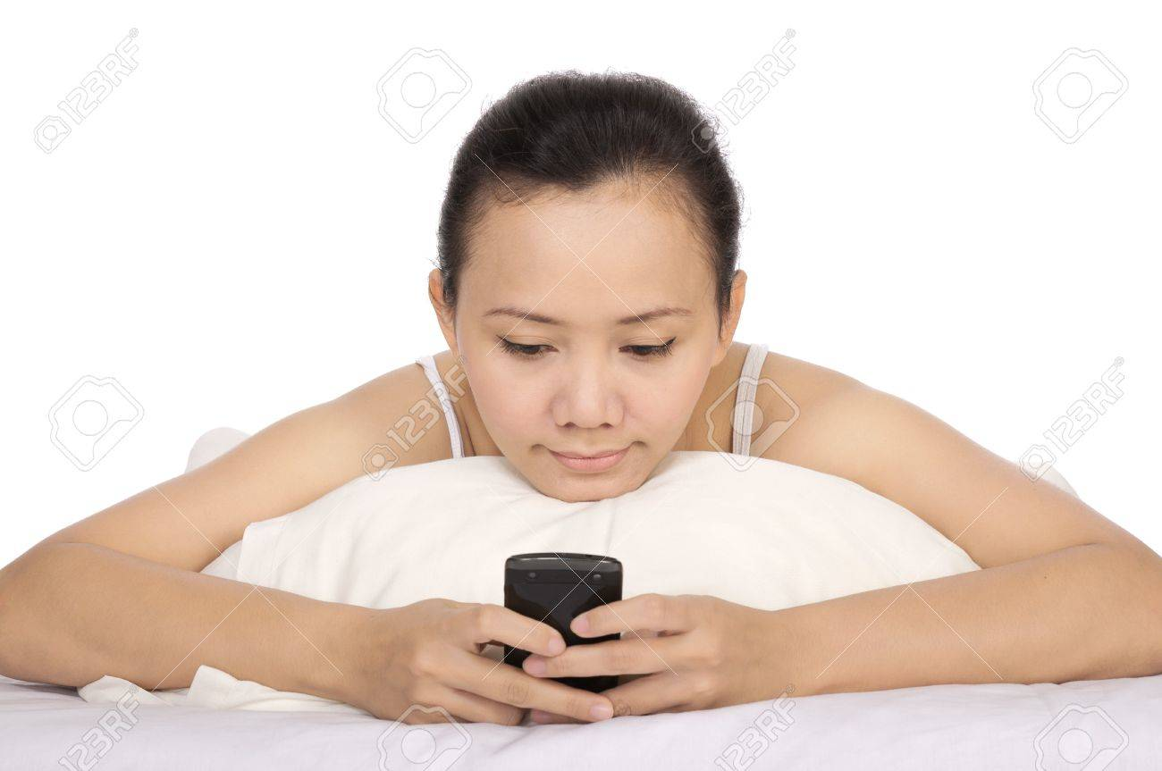 Asian woman send text message to her friend on the bed Stock Photo - 14431955