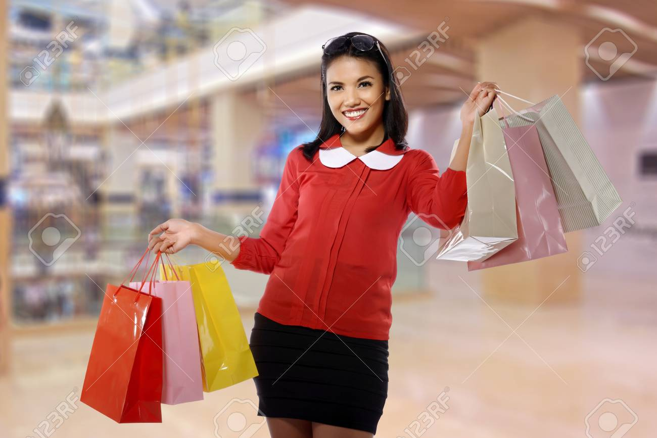 Portrait of young happy woman with shopping bags, with mall background Stock Photo - 21487579