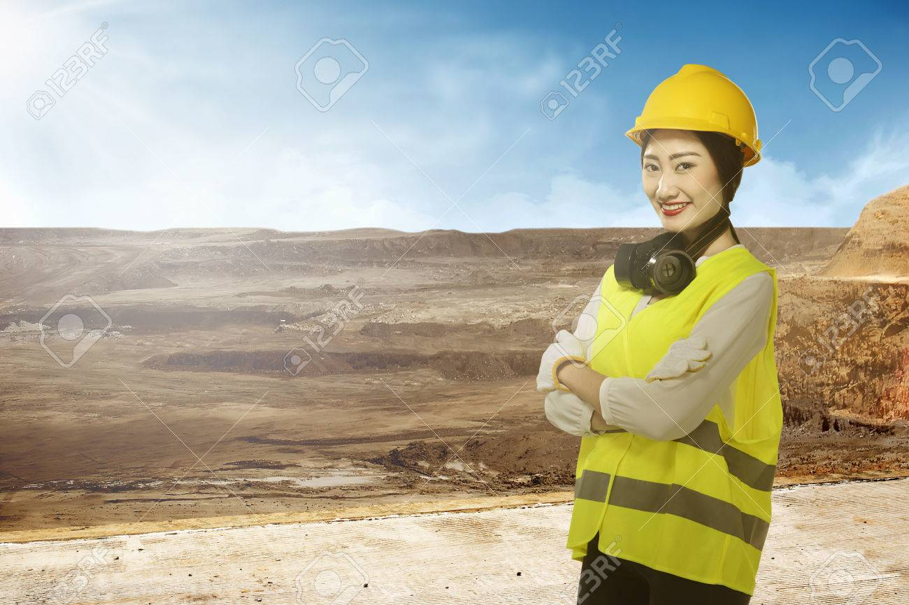 6819452e3c4 Asian business woman wearing yellow helmet smile over construction sites  background Stock Photo - 50401398