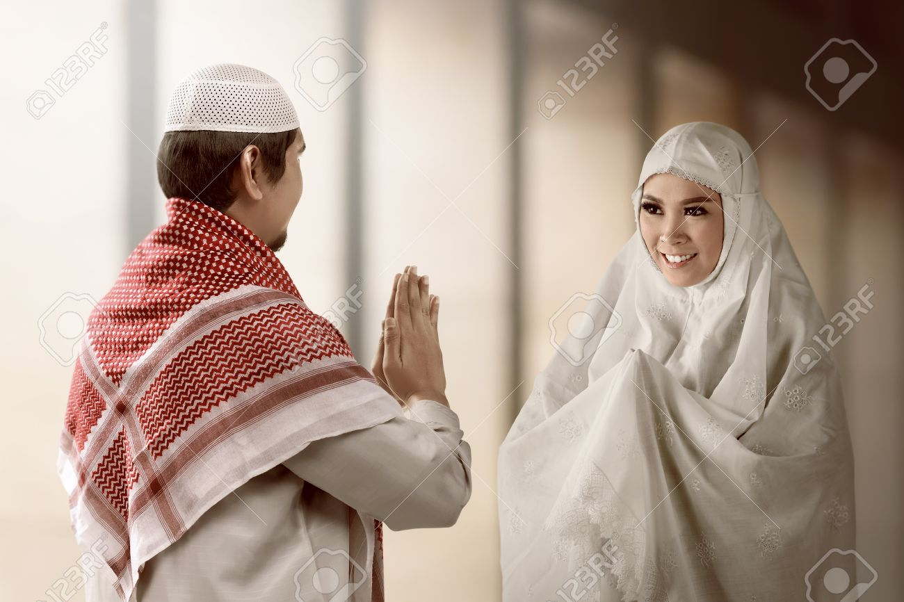 Asian muslim man and woman greet each other with muslim tradition asian muslim man and woman greet each other with muslim tradition with mosque background stock m4hsunfo