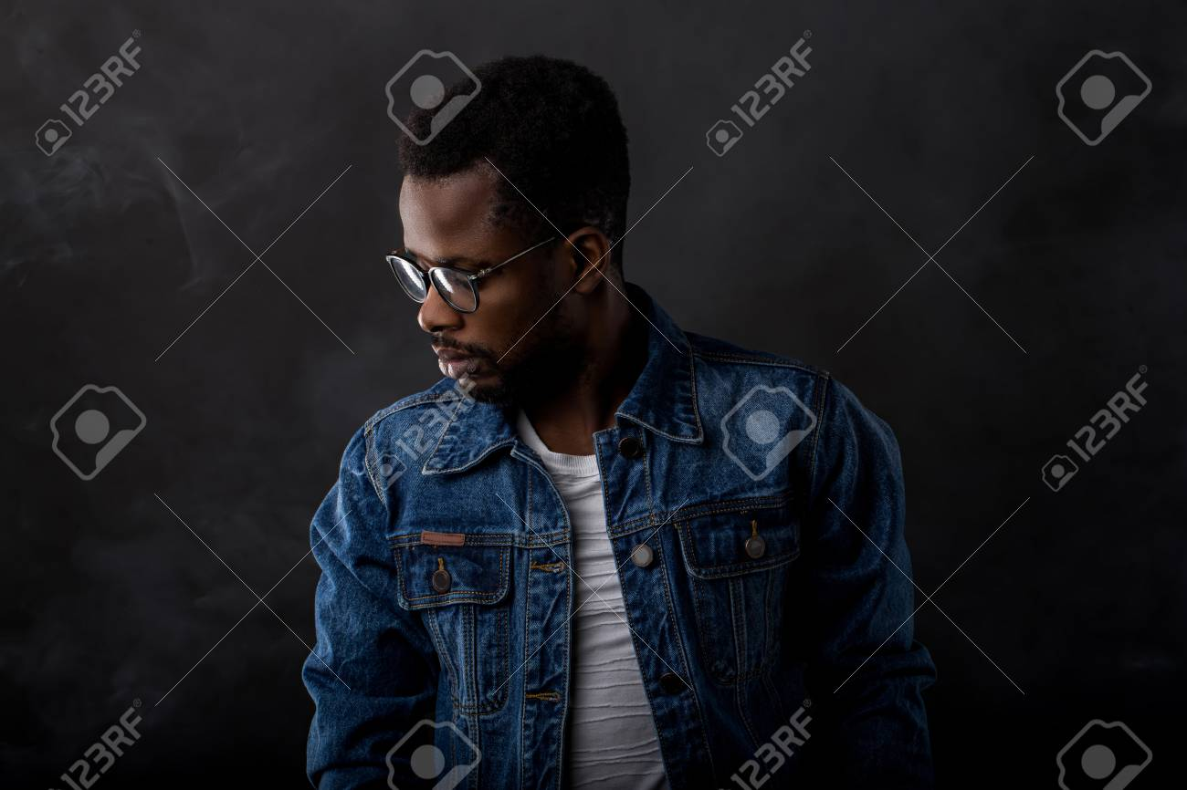 Cool and trendy. Portrait of handsome young African man in glasses wearing denim jacket ad white tshirt looking down while being in front of black background. - 123053427